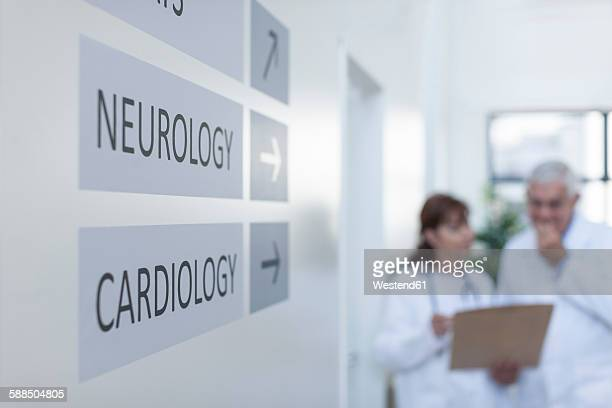 Direction signs on hospital wall with doctors in background