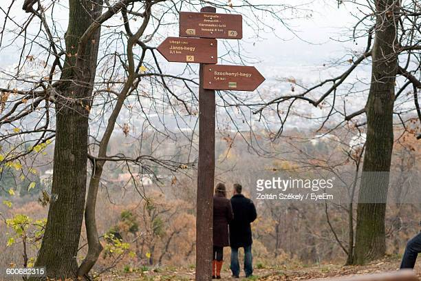 Directional Sign Against Couple In Forest