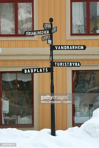 Directional Sign Board By Building On Snow Covered Sidewalk