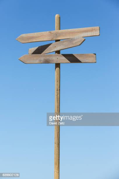 Directional signpost against sky