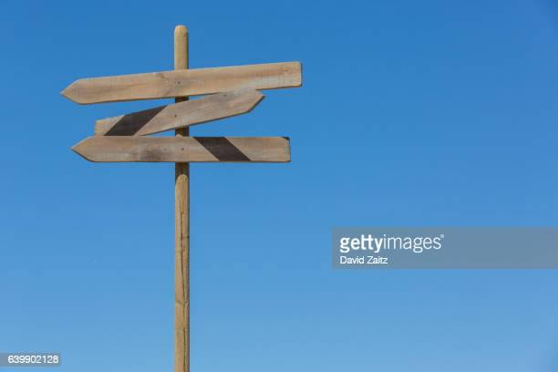 directional signpost against sky - post structure stock photos and pictures