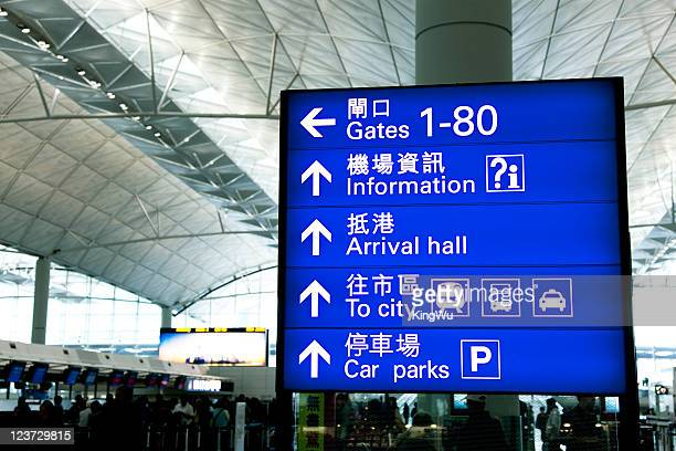 directional signs at airport - hong kong international airport stock photos and pictures
