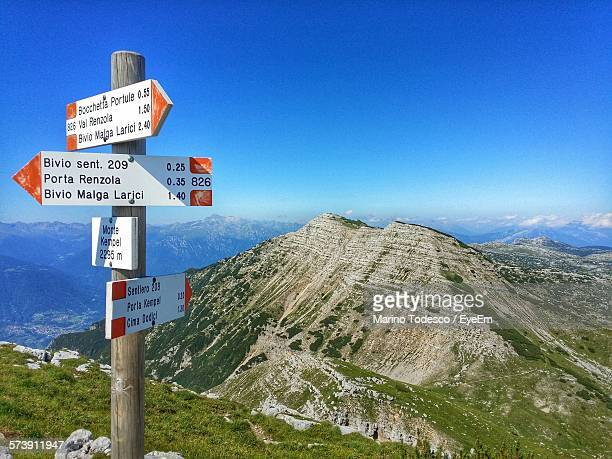 Directional Signs By Rocky Mountains Against Clear Blue Sky