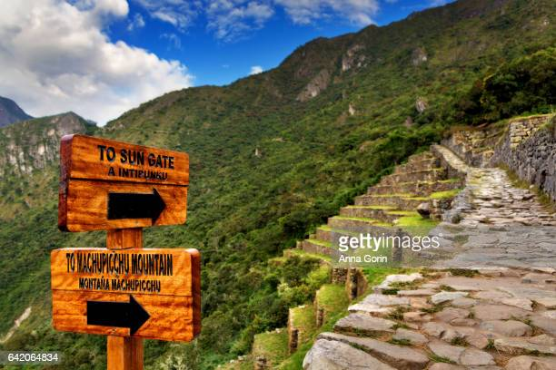 Directional signs to famous Sun Gate and Machupicchu Mountain with path in soft focus in background, Peru