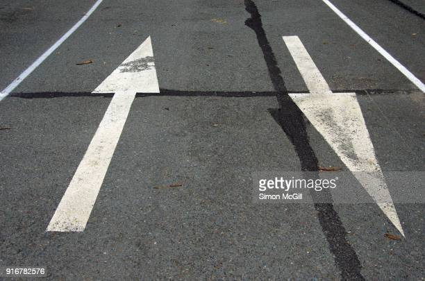 directional traffic arrows painted on a road - two lane highway stock pictures, royalty-free photos & images