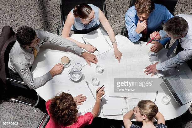 directly above business people pointing to paperwork on conference table in meeting - conferentietafel stockfoto's en -beelden
