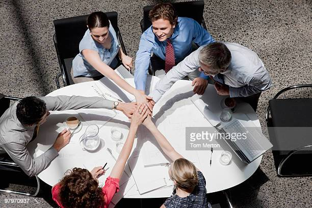 Directly above business people stacking hands in meeting at conference table