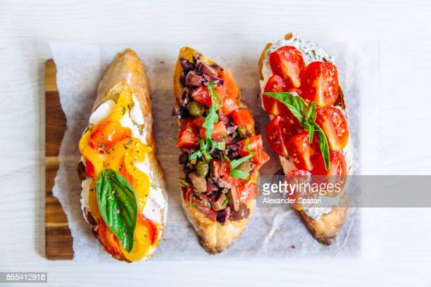 directly above close up shot of bruschettas with tomato, basil, capers, bell pepper and cheese - フランス料理 ストックフォトと画像