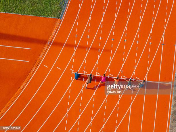 directly above drone point of view asian chinese athletes lining up getting ready starting line running at track and run towards finishing line in the morning at track and field stadium - forward athlete stock pictures, royalty-free photos & images