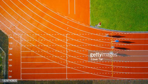 directly above drone point of view asian chinese male athlete running at men's track rainy late evening in stadium - forward athlete stock pictures, royalty-free photos & images