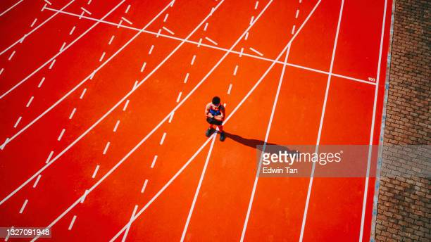 directly above drone point of view male asian chinese athlete standing at starting line arms crossed at track and field stadium - forward athlete stock pictures, royalty-free photos & images