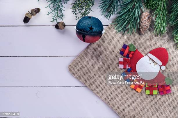 Directly above handmade rustic canvas bag with the figure of Santa Claus, pine cone, and Christmas ornaments on painted wooden background with copy space.