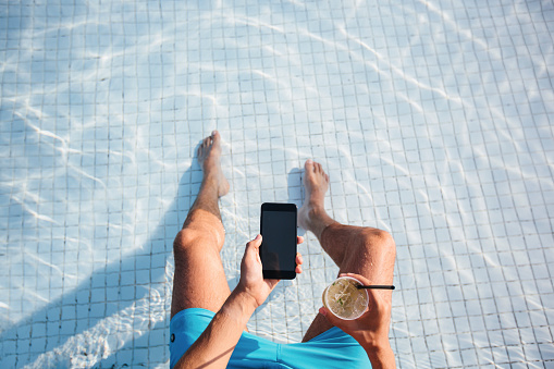 Directly above high angle view of a man using smart phone and drinking cocktail at the swimming pool - gettyimageskorea