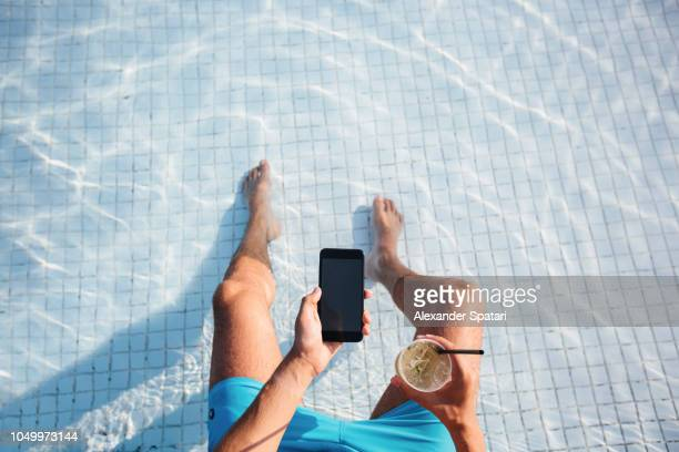 directly above high angle view of a man using smart phone and drinking cocktail at the swimming pool - poolside stock pictures, royalty-free photos & images
