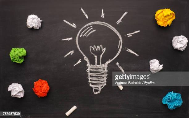 Directly Above Light Bulb Drawing Amidst Crumpled Colorful Papers On Blackboard