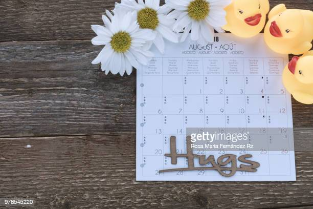 Directly above of calendar sheet,  three yellow daisies and three rubber ducks with work 'hugs' on old wooden background with copy space.