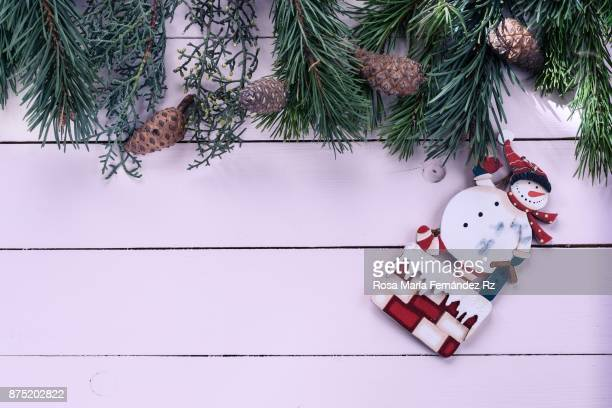 Directly above of Christmas ornaments (snowman shape), fir tree branches and pine cone on painted wooden background with copy space.