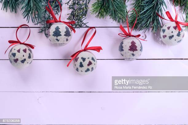 Directly above of collection of Christmas decoration balls and fir tree branches on painted wooden background with copy space.