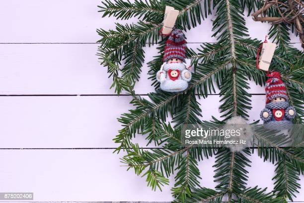 Directly above of fir tree branch and Christmas ornaments on painted wooden background with copy space.