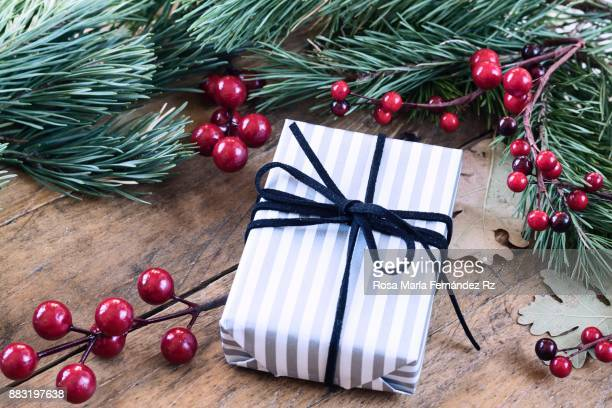 Directly above of gift box wrapped in gray and white striped paper framed with fir branches and mistletoe seeds on rustic wooden background. Selective focus.