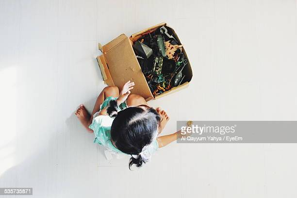 Directly Above Of Girl Playing With Toys While Sitting By Box At Home