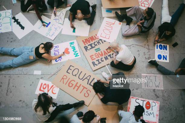 directly above of male and female activists preparing posters for social movement - civil rights stock pictures, royalty-free photos & images