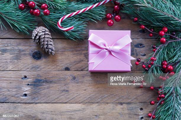 Directly above of wrapped christmas present, fir tree branches, mistletoe seed, candy can and pine cone on old wooden background. Copy space