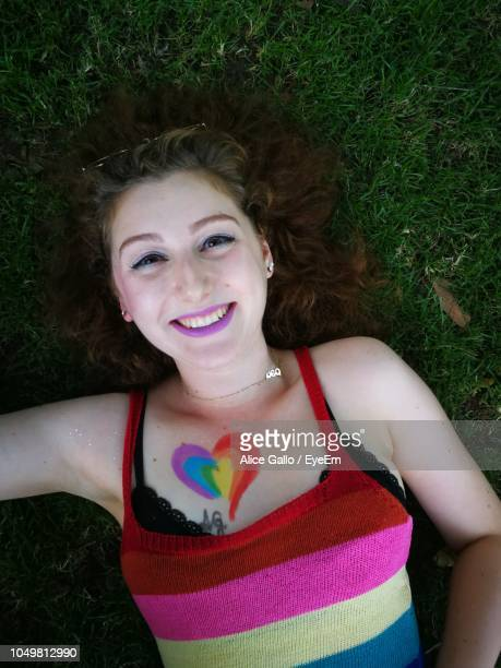 Directly Above Portrait Of Smiling Young Woman With Colorful Heart Drawn On Chest