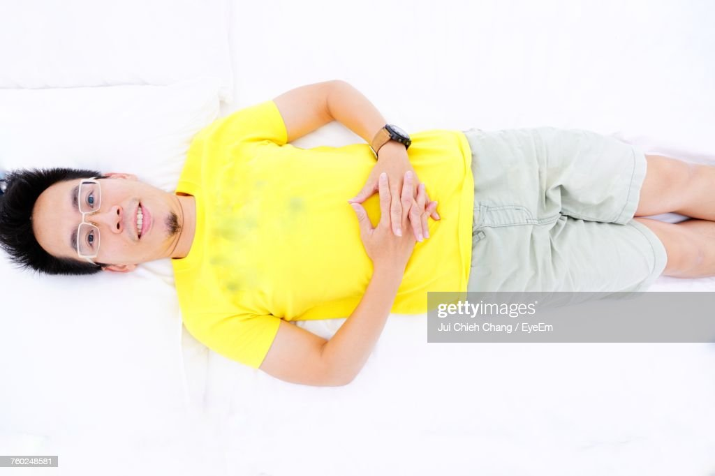 Directly Above Portrait Of Young Man Lying On White Bed : Stock Photo