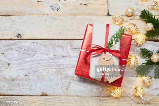 "directly above shot of a stack of wrapped christmas presents with ""for you"" gift tag on wooden background - craft product stock pictures, royalty-free photos & images"