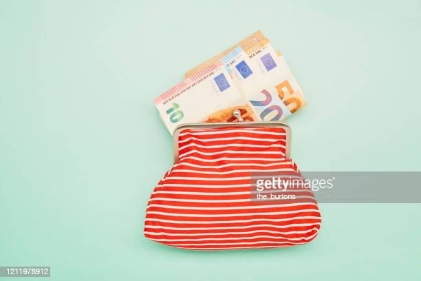 directly above shot of a wallet and euro banknotes on turquoise background - valuta europese unie stockfoto's en -beelden