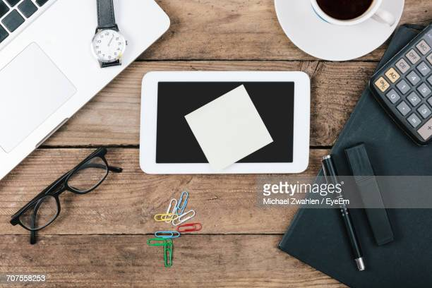 Directly Above Shot Of Adhesive Note And Digital Tablet Surrounded By Office Supplies On Table