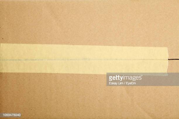 directly above shot of adhesive tape on cardboard box - carton stock photos and pictures