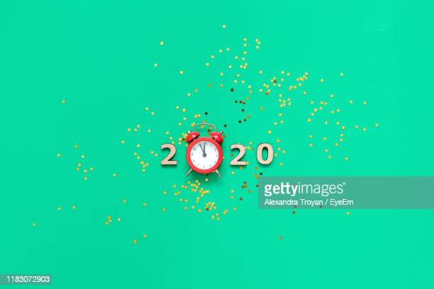 directly above shot of alarm clock over green background - new year 2020 stock photos and pictures
