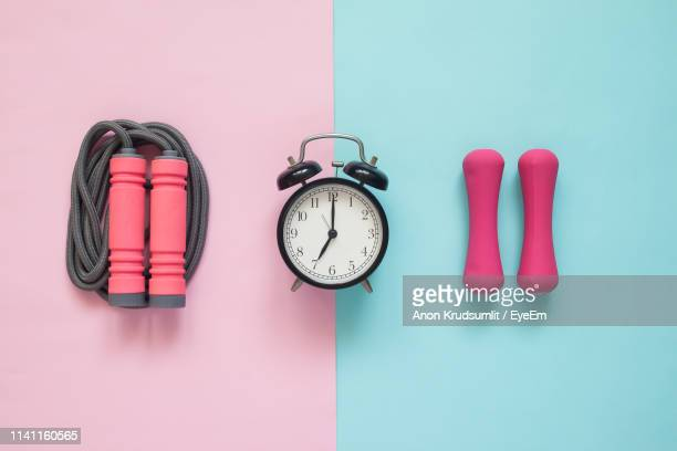 directly above shot of alarm clock with jump rope and dumbbells on colored background - dumbbell stock pictures, royalty-free photos & images
