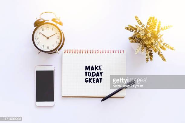 directly above shot of alarm clock with spiral notebook and smart phone on white background - wikipedia:citation stock pictures, royalty-free photos & images