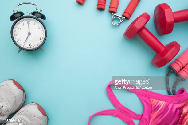 directly above shot of alarm clock with sports equipment on blue background - knolling concept stock pictures, royalty-free photos & images
