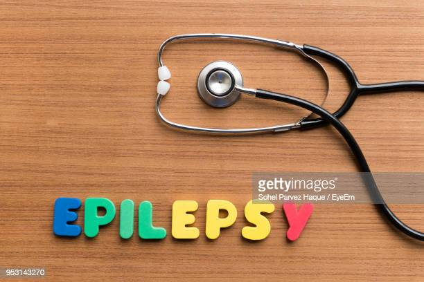 directly above shot of alphabets making epilepsy text by stethoscope on table - epilepsy stock pictures, royalty-free photos & images