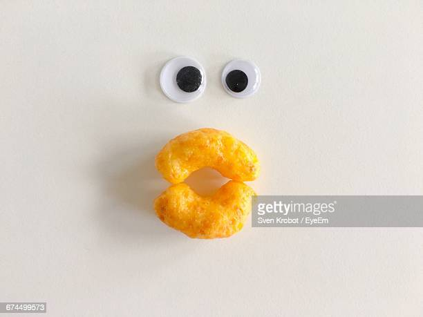 Directly Above Shot Of Anthropomorphic Face Made From Fried Food On White Background