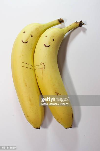 directly above shot of anthropomorphic face on bananas over white background - two objects stock photos and pictures