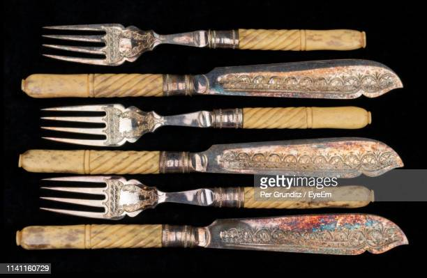 directly above shot of antique table knives and forks on black background - per grunditz stock pictures, royalty-free photos & images