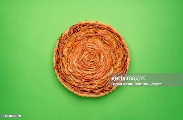 directly above shot of apple pie on green background - パイ ストックフォトと画像