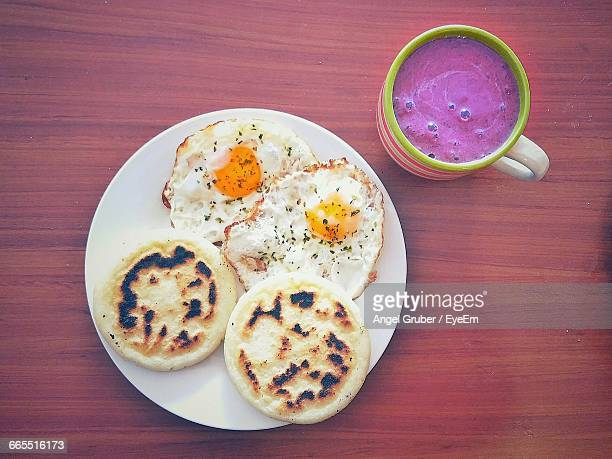 Directly Above Shot Of Arepas And Omelets In Plate By Blueberry Smoothie Served On Table