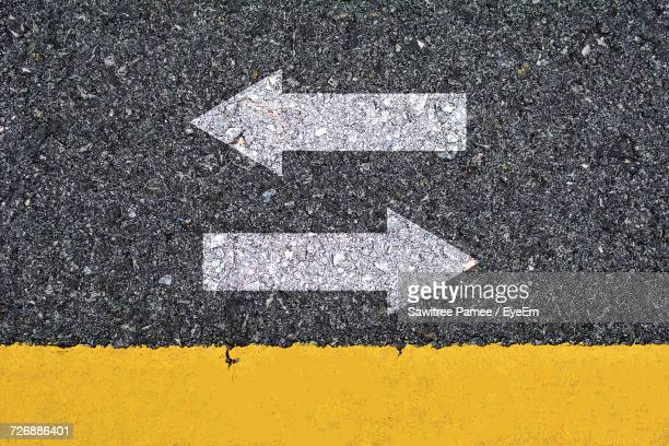 directly above shot of arrow symbols on road - marca de rua - fotografias e filmes do acervo