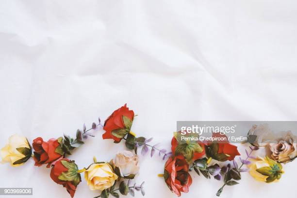 Directly Above Shot Of Artificial Roses On Fabric
