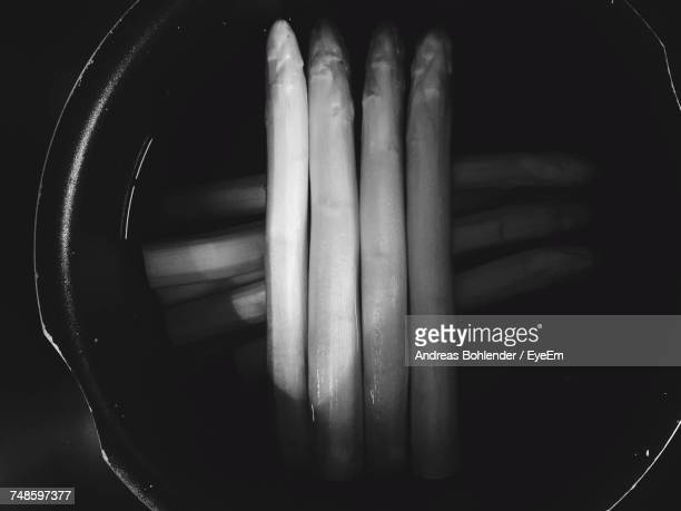 directly above shot of asparagus in bowl - black and white vegetables stock photos and pictures