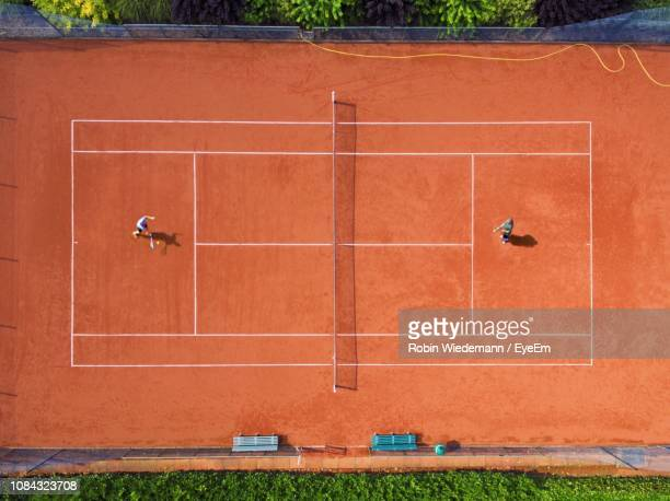 directly above shot of athletes playing tennis at court - draufsicht stock-fotos und bilder