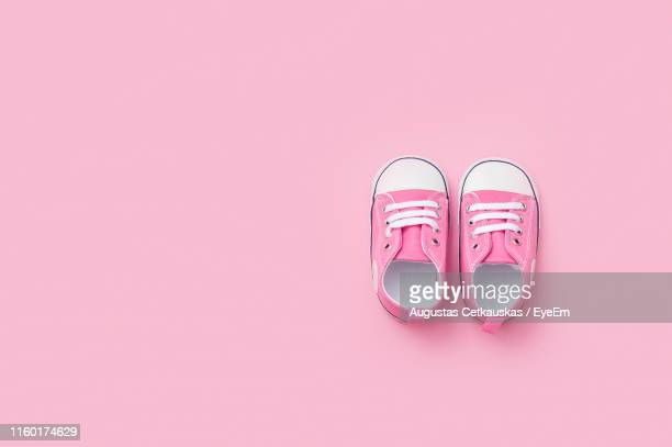 directly above shot of baby booties against pink background - shoelace stock pictures, royalty-free photos & images