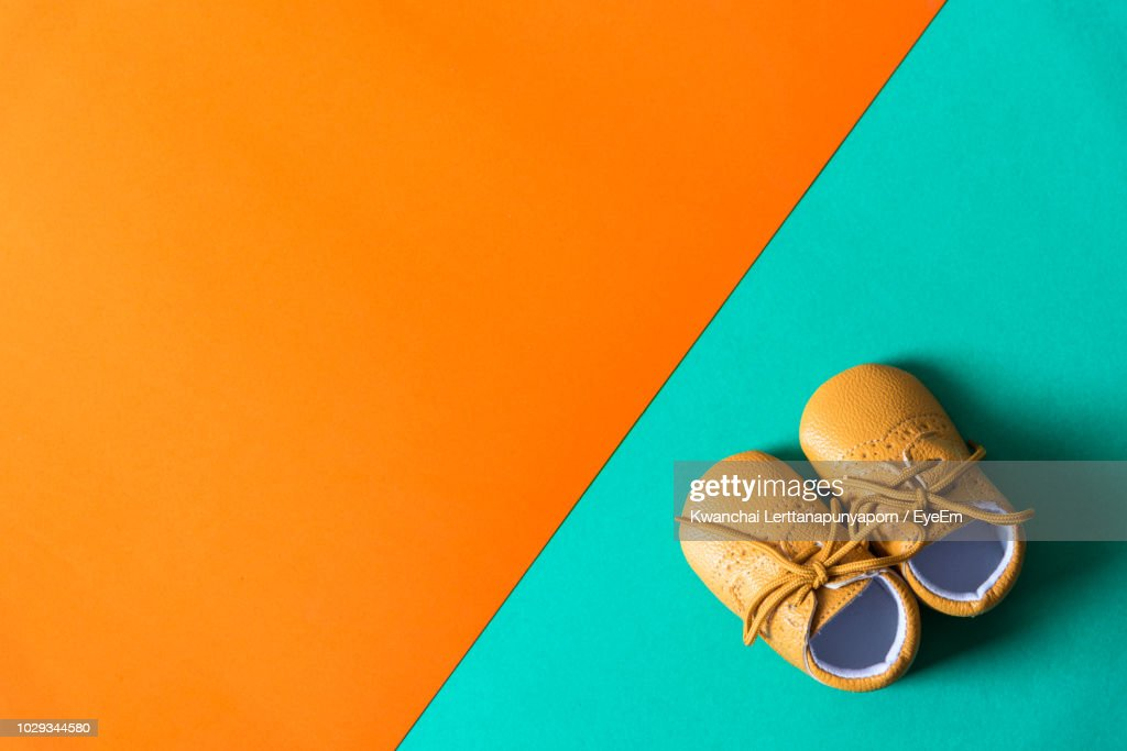 Directly Above Shot Of Baby Booties On Colored Background : Stock Photo