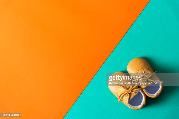 directly above shot of baby booties on colored background - baby booties stock photos and pictures
